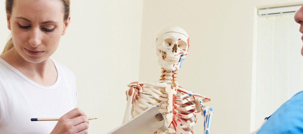 Image de fond Oxteo avec une femme ostéopathe qui prend des notes